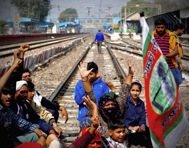 Farmers along with their family members shout slogans as they block railway tracks during a protest denouncing three farm laws approved by Parliament in September, in Sonepat, India, Thursday, February 18, 2021. Thousands of protesting farmers blocked trains on Thursday by sitting on railroad tracks in parts of northern India to press their demand for the repeal of new agricultural reform laws that have triggered months of massive protests. (Photo by Manish Swarup/AP Photo)