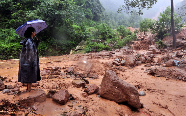 A woman looks on after a landslide triggered by heavy rainstorm hit Shanxi village of Zhongxing township in Dujiangyan, southwest China's Sichuan province on July 10, 2013. Between 30 and 40 people were buried by a landslide in southwest China on Wednesday, local officials said, as heavy rains in the area also destroyed homes and bridges. (Photo by AFP Photo)