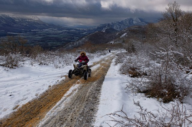 A woman rides a bike along a path as snow covers the landscape near Madotz in Spain on January 2, 2021. (Photo by Alvaro Barrientos/AP Photo)