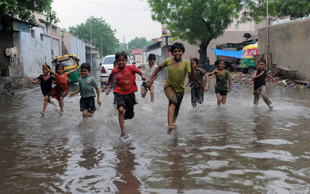 Indian children run across a flooded street in Ahmedabad on July 24, 2013. Heavy rains lashed many regions of Gujarat state and the Indian Meteorological Department (IMD) has warned of very heavy rains in Gujarat and surrounding regions in next 36 hours. (Photo by Sam Panthaky/AFP Photo)