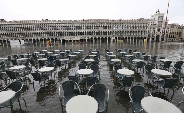 Empty tables and chairs are seen on the flooded St. Mark's Square during a period of seasonal high water and on the first day of carnival, in Venice February 1, 2015. (Photo by Stefano Rellandini/Reuters)