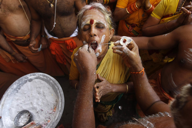 A Hindu woman devotee gets her cheeks pierced with a metal rod as she participates in a religious procession during Thaipusam festival in Chennai, India, Tuesday, February 3, 2015. (Photo by Arun Sankar K./AP Photo)