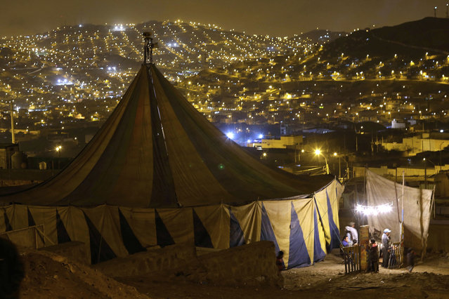 """In this July 8, 2018 photo, homes in the Puente Piedra shantytown light up the landscape around the Tony Perejil circus set up on the outskirts of Lima, Peru. The circus' owner Jose Alvarez, a 52-year-old businessman, said """"Lima is lousy"""" for his circus, and that he'll move it north toward Peru's border with Ecuador. (Photo by Martin Mejia/AP Photo)"""