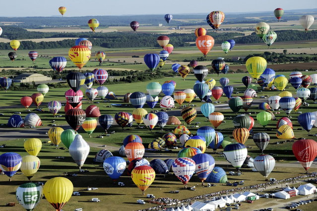 "Over 400 hot-air balloons take off in Chambley-Bussieres, eastern France, on Wednesday, July 31, 2013 in an attempt to set a world record for collective taking-off during the event ""Lorraine Mondial air ballons"", an international hot-air balloon meeting. (Photo by Alexandre Marchi/AP Photo/L'est Republicain)"