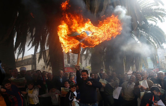 A Palestinian protester burns an Israeli flag on November 20, 2016 in the West Bank city of Nablus, during a rally gathering Muslims, Christians and Samaritans to protest against an Israeli draft bill that would limit the volume of calls to prayer at mosques in Israel and Jerusalem. (Photo by Jaafar Ashtiyeh/AFP Photo)