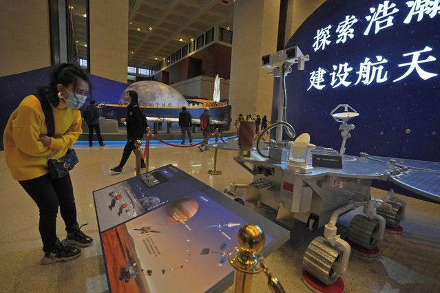 """A visitor to an exhibition looks at a display with a replica of the Chinese Mars Rover of the Tianwen-1 spacecraft in Beijing on March 12, 2021. China's National Space Agency confirmed Wednesday, March 31, 2021 that it had working-level meetings and communications with NASA from January to March """"to ensure the flight safety"""" of their crafts. (Photo by Ng Han Guan/AP Photo)"""