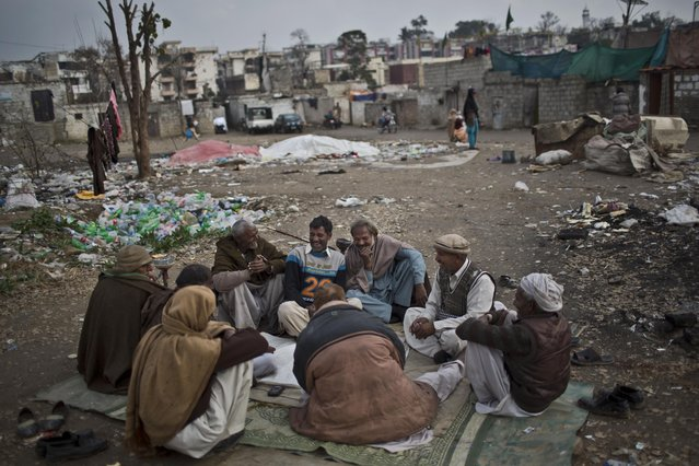 In this Tuesday, February 3, 2015 photo, Pakistani Christian men play cards at a slum home to Christian families in Islamabad, Pakistan. (Photo by Muhammed Muheisen/AP Photo)