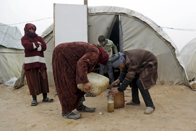 A woman pours kerosene inside a bottle to be used for heating in Jerjnaz camp, for internally displaced people, during the cold weather in Idlib province, Syria, January 5, 2016. (Photo by Khalil Ashawi/Reuters)