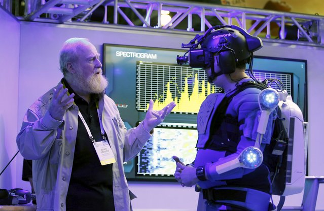 Bran Ferren (L), founder of Applied Minds, talks to a journalist dressed in an R70i aging suit during a preview of the Genworth booth at the 2016 CES trade show in Las Vegas, Nevada, January 5, 2016. (Photo by Steve Marcus/Reuters)