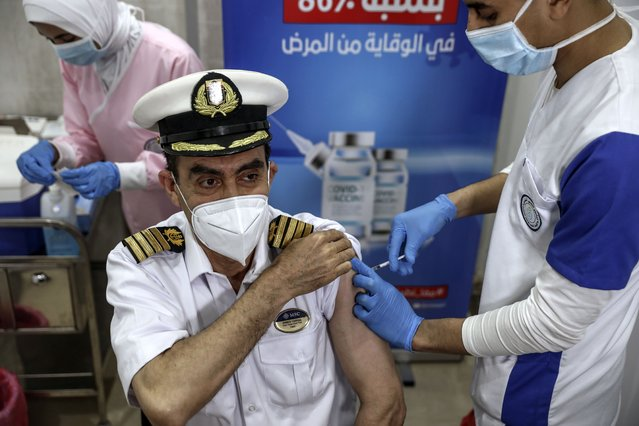 A Suec Cana pilot receives a COVID-19 vaccine in Ismailia, Egypt, Tuesday, April 6, 2021. The Suez Canal chief said Tuesday that authorities are negotiating a financial settlement with the owners of a massive vessel that blocked the crucial waterway for nearly a week. (Photo by Mohamed Elshahed/AP Photo)