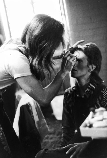 Make-up artist Pierre La Roche prepares English singer David Bowie for a performance as Aladdin Sane, 1973. (Photo by Daily Express/Hulton Archive/Getty Images)