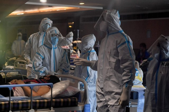 Health workers wearing personal protective equipment (PPE kit) attends to Covid-19 coronavirus positive patients inside a banquet hall temporarily converted into a covid care centre in New Delhi on April 29, 2021. (Photo by Tauseef Mustafa/AFP Photo)
