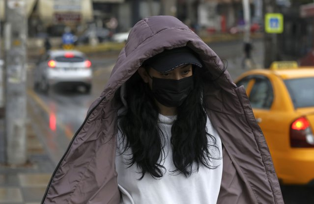 A woman wearing a mask to help protect against the spread of coronavirus, walk in the rain in Ankara, Turkey, Monday, March 29, 2021. Turkey is reinstating weekend lockdowns in most of Turkey's provinces and will also impose restrictions over the Muslim holy month of Ramadan following a sharp increase in COVID-19 cases. (Photo by Burhan Ozbilici/AP Photo)