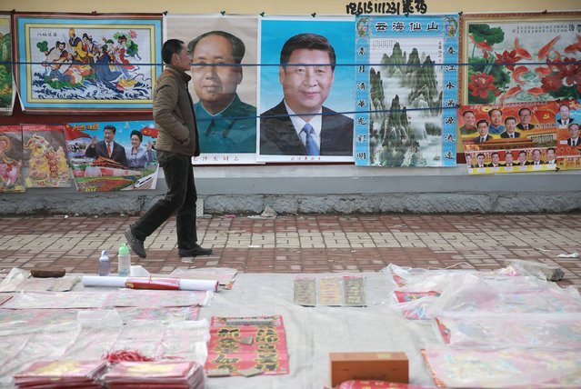 A man walks past New Year decoration pictures featuring China's President Xi Jinping, China's late Chairman Mao Zedong and some other current senior officials, at a market in Juancheng, Shandong province, February 17, 2015. (Photo by Reuters/Stringer)