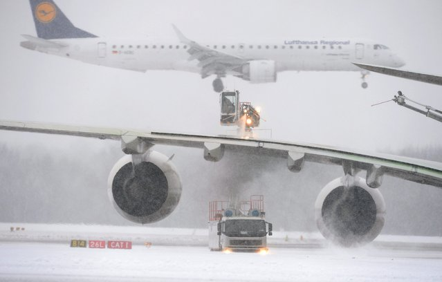 An airplane is cleared of snow and ice, while an airplane lands in the background at the snowcapped airport in Munich, Germany, 30 December 2014. 45 take-offs and landings were cancelled due to weather conditions so far. (Photo by Andreas Gebert/EPA)