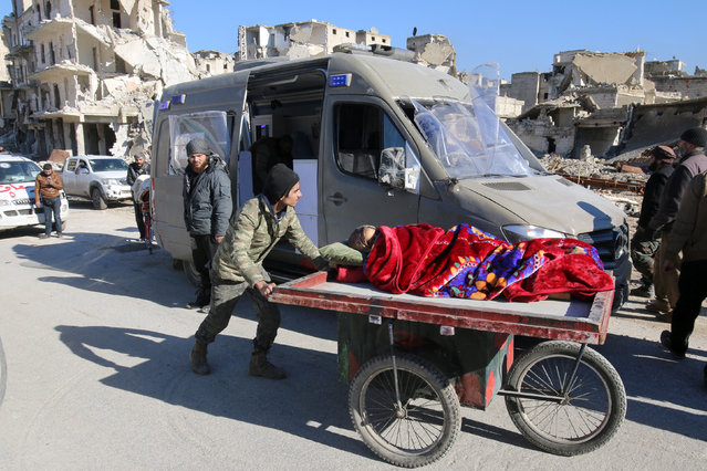 A man pushes a cart with a woman lying on it as vehicles wait to evacuate people from a rebel-held sector of eastern Aleppo, Syria December 15, 2016. (Photo by Abdalrhman Ismail/Reuters)