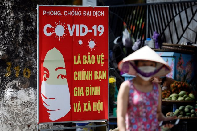 A woman walks past a sign reading 'Preventing and fighting against COVID-19 pandemic is protecting yourself, your family and society', in Hanoi, Vietnam 01 June 2021. Vietnam suspends incoming international flights to the capital city of Hanoi from 01 June 2021 to prevent the spread of the COVID-19 pandemic amid rising number of cases. (Photo by Luong Thai Linh/EPA/EFE)
