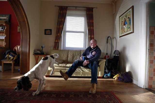Fr Pierre Pepper drinks a cup of tea with his rescue dog Cosmo in the Parochial House next to St Rynagh's Roman Catholic Church in the village of Banagher County Offaly March 2, 2015. (Photo by Cathal McNaughton/Reuters)