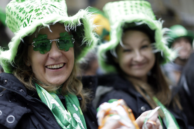 Mareike Stibbe, left, of Waldeck, Germany and Justine Poloczek of Marburg, Germany watch participants march up Fifth Ave. during the St. Patrick's Day Parade, Tuesday, March 17, 2015, in New York. (Photo by Mary Altaffer/AP Photo)