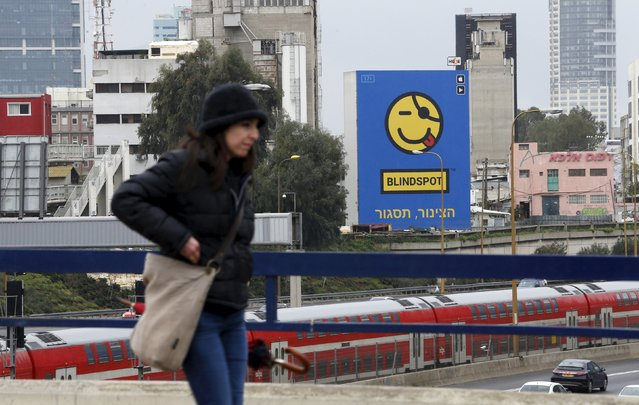 A woman walks past a billboard advertisement for Israeli app Blindspot, which allows people to send text messages anonymously, in Tel Aviv January 25, 2016. The Israeli anonymous messaging app billed as providing a voice to those who are too shy or scared to communicate openly has set off alarms among parents and politicians who see in it a stealth weapon for cyber-bullying. (Photo by Baz Ratner/Reuters)