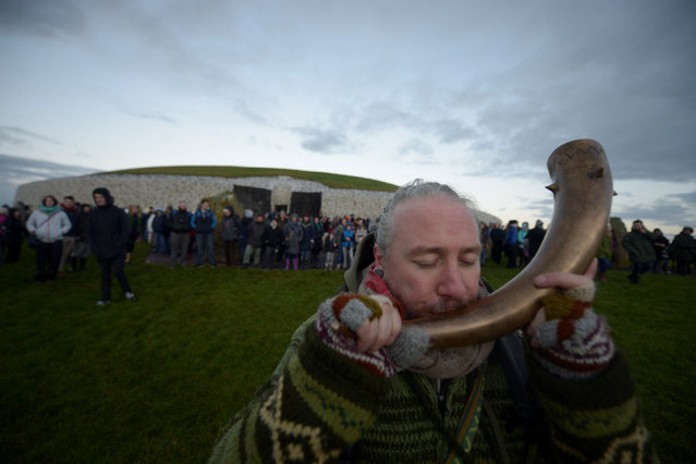 A reveller celebrates winter solstice at the 5000 year old stone age tomb of Newgrange in the Boyne Valley at sunrise in Newgrange, Ireland, December 21, 2016. (Photo by Clodagh Kilcoyne/Reuters)
