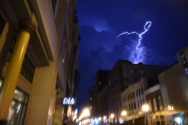 Lightning strikes over downtown in Knoxville, Tenn., on Sunday, July 27, 2014. Authorities say powerful storms crossing east Tennessee have destroyed 10 homes and damaged others, though there are no immediate reports of any deaths or injuries. (Photo by Saul Young/AP Photo/The Knoxville News Sentinel)
