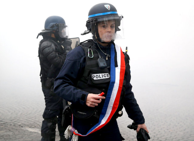A policewoman wearing a tricolour sash braves the teargas in Paris, France on November 24, 2018. Thousands had travelled from across France to show their anger at the French president, Emmanuel Macron, and the government. The interior minister, Christophe Castaner, said 8,000 protesters had arrived in Paris by mid-morning, 5,000 of them on the Champs Élysées, which had been closed off. (Photo by Mchiche/News Pictures/Rex Features/Shutterstock)