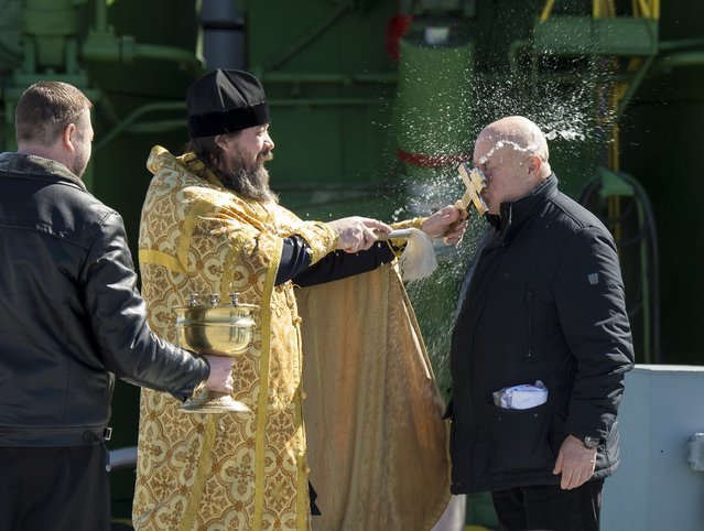 An Orthodox Priest blesses Sergey Semchenko of the Russian Search and Recovery Forces after having blessed the Soyuz rocket at the Baikonur Cosmodrome Launch pad on March 26, 2015 in Kazakhstan. (Photo by Bill Ingalls/AFP Photo)
