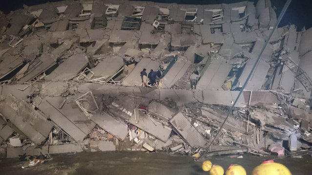 Rescuers are seen entering an office building that collapsed on its side from an early morning earthquake in Tainan, southern Taiwan, Saturday, February 6, 2016. (Photo by AP Photo)