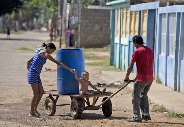 In this August 20, 2018 photo, a family plays with their son after they collected drinking water in a plastic drum from a public fountain, in Cabimas, Venezuela. For months Maracaibo's residents have endured rolling blackouts. Basic services like running water and electricity have become a luxury. (Photo by Fernando Llano/AP Photo)