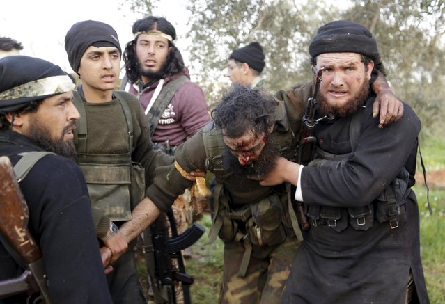 Rebel fighters from the Ahrar al-Sham Islamic Movement help an injured fellow fighter during what they said was an offensive to take the northwestern city of Idlib March 24, 2015. (Photo by Khalil Ashawi/Reuters)