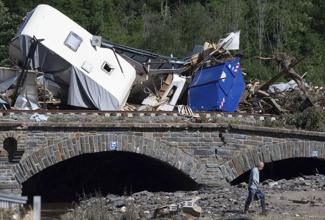 Caravans, cars and mobile homes that were swept away by the flood wave hang together on a bridge over the River Ahr, in Altenahr, western Germany, Sunday, July 18, 2021. Heavy rains caused mudslides and flooding in the western part of Germany. Multiple have died and are missing as severe flooding in Germany and Belgium turned streams and streets into raging, debris-filled torrents that swept away cars and toppled houses. (Photo by Boris Roessler/dpa via AP Photo)