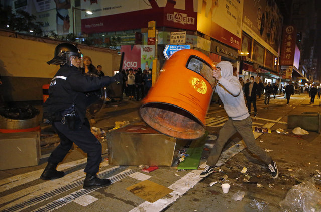 A rioter tries to throw a litter bin at police on a street in Mong Kok district of Hong Kong, Tuesday, February 9, 2016. (Photo by Kin Cheung/AP Photo)