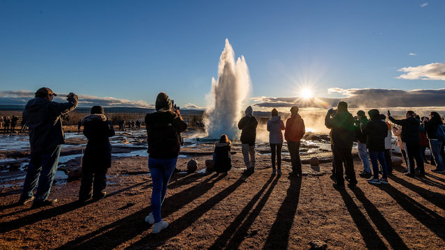 """Strokkur geyser with people watching as the spout of water erupts about every 10 minutes to varying heights, Haukadalur valley, Iceland on November 20, 2018. Geysir sometimes known as The Great Geysir, is a geyser in southwestern Iceland. It was the first geyser described in a printed source and the first known to modern Europeans.The English word geyser (a periodically spouting hot spring) derives from Geysir. The name Geysir itself is derived from the Icelandic verb geysa (""""to gush"""") the verb from Old Norse. Geysir lies in the Haukadalur valley on the slopes of Laugarfjall hill, which is also the home to Strokkur geyser about 50 metres (160 ft) south. Eruptions at Geysir can hurl boiling water up to 70 metres (230 ft) in the air. However, eruptions may be infrequent, and have in the past stopped altogether for years at a time. (Photo by Charlotte Graham/Rex Features/Shutterstock)"""