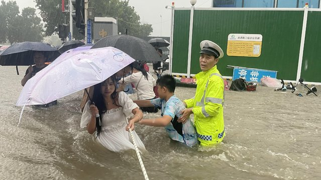 A traffic police officer guides residents to cross a flooded road with a rope during heavy rainfall in Zhengzhou, Henan province, July 20, 2021. (Photo by China Daily via Reuters)