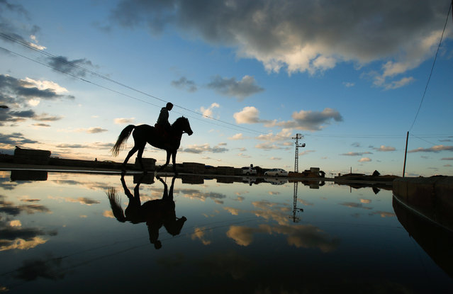 A Palestinian rides a horse along a flooded path in the northern of Gaza Strip December 17, 2016. (Photo by Suhaib Salem/Reuters)
