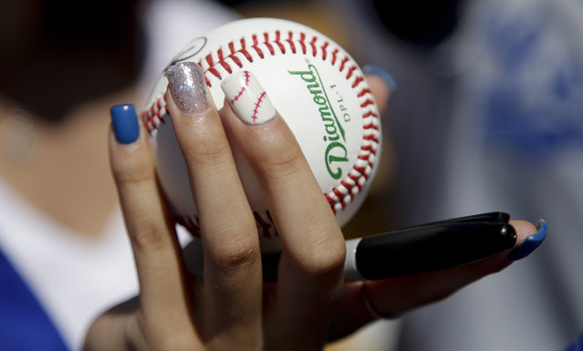 A fan sporting baseball themed finger nails waits for autographs before a spring training baseball exhibition game between the Chicago White Sox and the Los Angeles Dodgers in Glendale, Ariz., on Tuesday, March 31, 2015. (Photo by Chris Carlson/AP Photo)