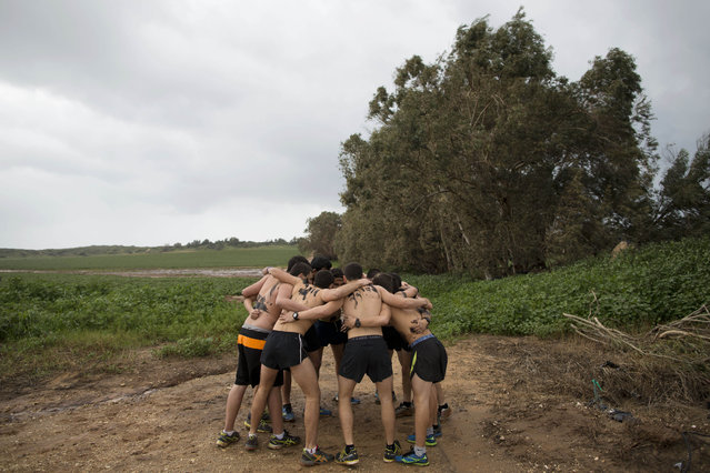 In this Friday, February 13, 2015 photo, Israeli high-school seniors preparing to join the Israeli military later this year huddle during an exercise at a privately run training camp for military combat fitness near Yakum, central Israel. (Photo by Oded Balilty/AP Photo)