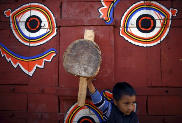 A boy stands in front of the chariot of Hindu god Bhairab before helping to pull the chariot during the Bisket festival at Bhaktapur April 10, 2015. (Photo by Navesh Chitrakar/Reuters)