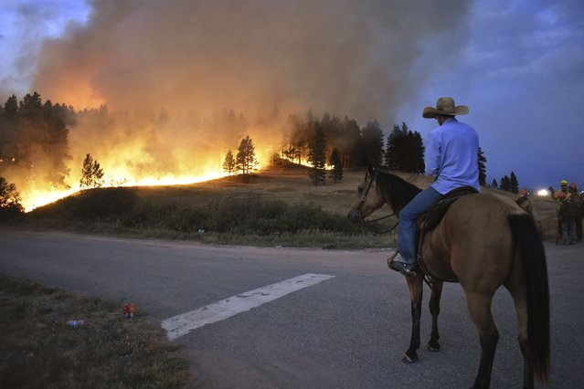 Rowdy Alexander watches from atop his horse as a hillside burns on the Northern Cheyenne Indian Reservation, Wednesday, August 11, 2021, near Lame Deer, Mont. The Richard Spring fire was threatening hundreds of homes as it burned across the reservation. (Photo by Matthew Brown/AP Photo)