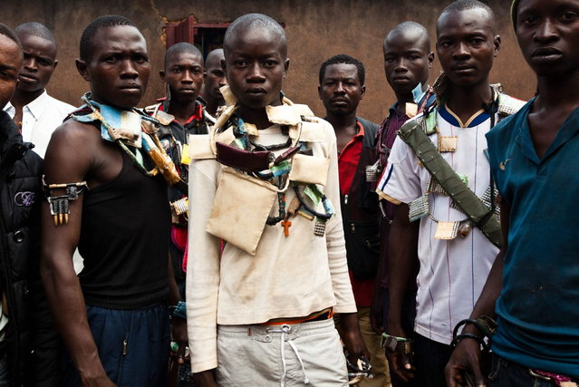 Anti-Balaka fighters, members of a militia opposed to the Seleka rebel group, pose with weapons and amulets in a village in the Boy-Rabe neighborhood in Bangui on December 14, 2013. (Photo by Ivan Lieman/AFP Photo)