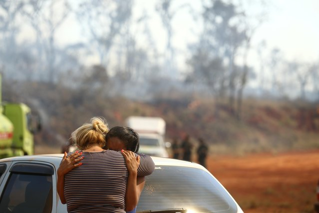 Two women cry as fire consumes the vegetation, after a hot air balloon crashed into the Juquery State Park, according to fire authorities, in Franco da Rocha, near Sao Paulo, Brazil, August 23, 2021. (Photo by Carla Carniel/Reuters)