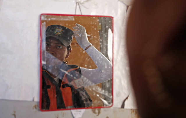 In this November 28, 2013 photo, the image of an Aymara woman adjusting her khaki green police-style cap is reflected in a mirror in El Alto, Bolivia. (Photo by Juan Karita/AP Photo)