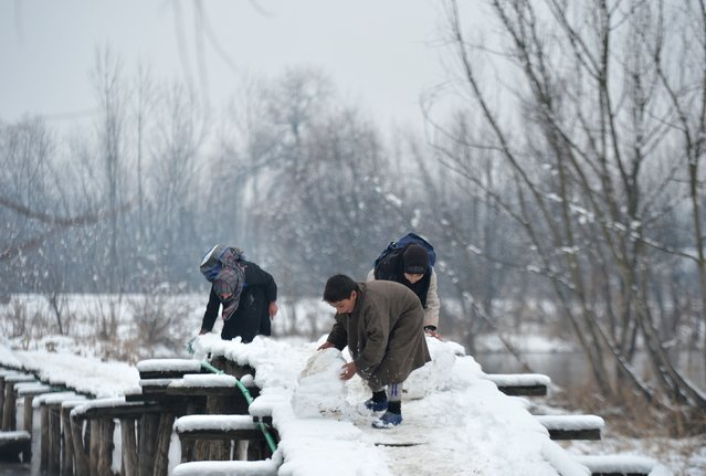 Kashmiri children play with snow on a wooden foot bridge in the interiors of Dal Lake in Srinagar on January 16, 2017. (Photo by Tauseef Mustafa/AFP Photo)