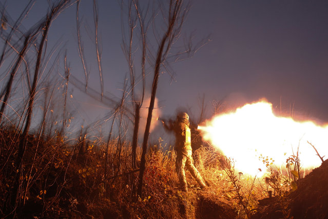 A Ukrainian serviceman shoots with a grenade launcher during a night combat with Russia- backed separatists uptown of Avdiivka, Donetsk region on November 3, 2018. The four- year conflict between pro- Russian separatists and the Ukrainian army has left more than 10,000 people dead since 2014. (Photo by Anatolii Stepanov/AFP Photo)