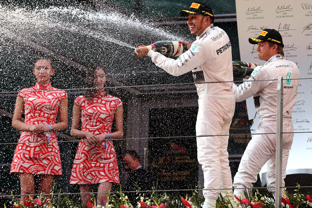 British Formula One driver Lewis Hamilton (C) celebrates with second placed German Formula One driver Nico Rosberg (R) of Mercedes AMG GP after winning the Chinese Formula One Grand Prix at the Shanghai International circuit in Shanghai, China, 12 April 2015. (Photo by Wu Hong/EPA)