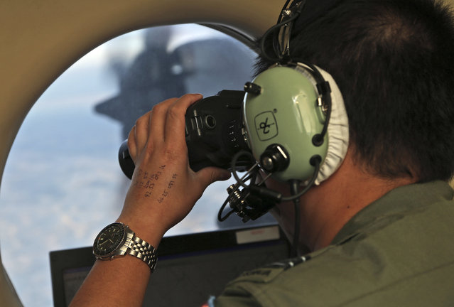 In this image of March 22, 2014, flight attendant Jack Chen uses binoculars in an observation window of an Australian Air Force P-3 Orion aircraft, during the search for the missing Malaysia Airlines MH370 aircraft in the south of the country. Indian Ocean, Australia. The Joint Agency Coordination Center in Australia, which helped lead the $160 million hunt for the Boeing 777 in remote waters west of Australia, said Tuesday the search had officially been suspended after crews finished their fruitless sweep of the 120,000-square kilometer (46,000-square mile) search zone. (Photo by Rob Griffith/AP Foto)
