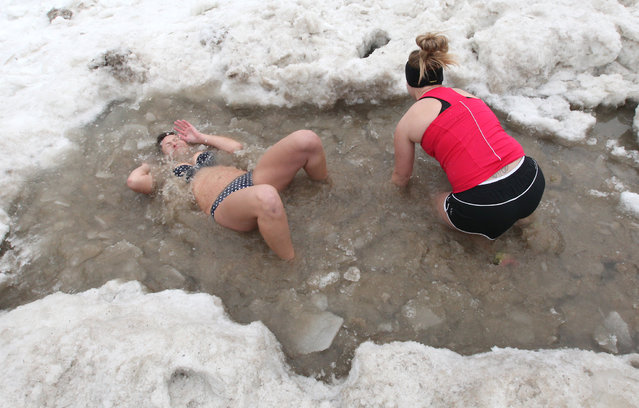 Resl Weigel, (left) of Milwaukee submerges herself in freezing cold water. The annual Polar Bear Plunge in Milwaukee was held at Bradford Beach on Wednesday, January 1, 2014. (Photo by Mike De Sisti)