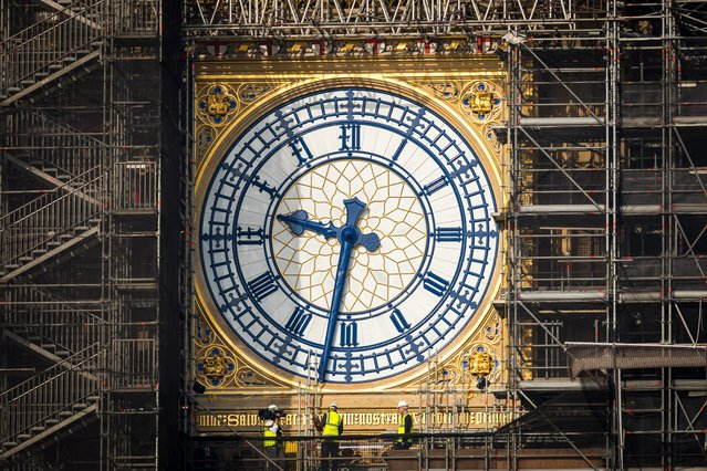 Workers stand on scaffolding underneath the clock face on the Elizabeth Tower, known as Big Ben with the clock hands seen restored to the original Prussian blue colouring in London, Britain, 06 September 2021. Members of Parliament return to the House of Commons after the summer recess today, 06 September 2021. (Photo by Vickie Flores/EPA/EFE)