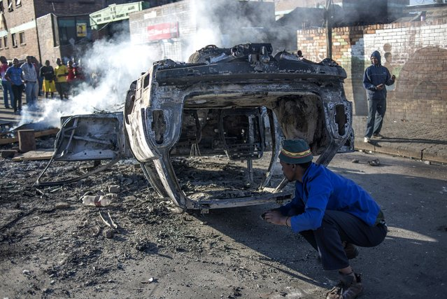 People lok at a burnt-out car after foreign nationals purportedly torched it in the early hours outside the Jeppies Hostles, in the Jeppestown area of Johannesburg, on April 17, 2015. (Photo by Mujahid Safodien/AFP Photo)